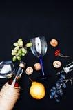 La vida inmóvil con el vino blanco en la botella de cristal en fondo negro Vidrios de vino con las uvas frescas Botella y vidrio  Imagen de archivo