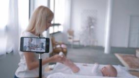 La video fucilazione del blog, giovane madre utilizza uno smartphone ed insegna a come fare gli esercizi per il neonato sul cambi stock footage