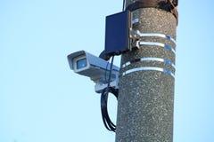 La videocamera nel rivestimento termico sigillato sul sostegno è riparata su una colonna della strada cementata immagini stock