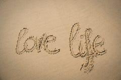 La vie amoureuse de mots écrite dans le sable Image stock