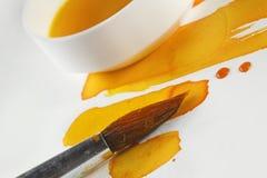 La vie artistique avec des pots de couleur teintait toujours l'eau avec une brosse Images libres de droits