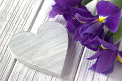 La vie avec l'iris de signe de coeur fleurit toujours sur le fond en bois blanc mariage Photographie stock