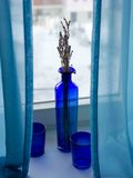 La vie avec les verres bleus et un vase toujours se tenant sur le rebord de fenêtre pendant l'hiver aménagent en parc Photos stock