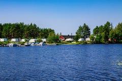 La vie de camping avec des caravanes en parc naturel par le lac Photographie stock libre de droits