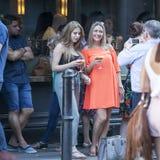 La vie du café de rue Fille de sourire bouclée parlant avec des amis en dehors de barre Photographie stock