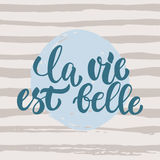 La vie est belle - hand drawn French lettering phrase it means Life is beautiful  on striped grunge background Stock Images