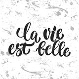 La vie est belle - hand drawn French lettering phrase, it means Life is beautiful,  on the white grunge Stock Image