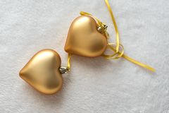 La vie immobile de Noël avec amour pour aimé, deux coeurs d'or sur un ruban d'or sur un fond clair Cadeau de jour du ` s de Valen image stock