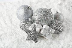 La vie immobile de Noël avec les boules, l'étoile argentée et les boîte-cadeau se trouvant sur la neige d'hiver sur un fond blanc photo libre de droits