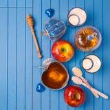 La vie juive de Rosh Hashana toujours de vacances avec du miel, des pommes et des bougies sur la table bleue en bois Vue de ci-av Images stock