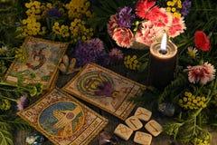 La vie toujours avec de vieilles cartes de tarot, bougie noire, runes, herbes curatives et fleurs image stock