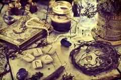 La vie toujours avec de vieilles cartes de tarot, runes, racines et bougie noire sur la table images libres de droits