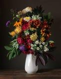 La vie toujours avec des asters et des chrysanthèmes dans une cruche blanche image libre de droits