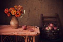 La vie toujours avec des fleurs et des pommes sur le vieux mur de fond images stock