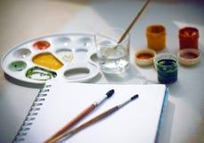 La vie toujours avec des peintures de gouache, une palette, un carnet, des brosses et un verre de l'eau image libre de droits