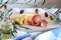 La vie toujours avec l'Espagnol un jamon, olives et huile d'olive dans une bouteille sur une planche à découper en bois Photos stock
