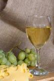 La vie toujours avec le verre de vin blanc, de fromage et de raisins Photos libres de droits