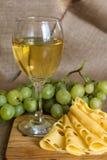 La vie toujours avec le verre de vin blanc, de fromage et de raisins Photo stock