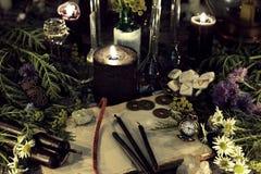 La vie toujours avec le vieux livre, l'horloge antique, les herbes, les bougies noires et les objets rituels photographie stock