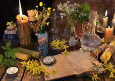 La vie toujours avec le vieux livre, les bougies, les bouteilles en verre et les herbes curatives Image libre de droits