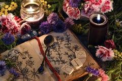 La vie toujours avec le vieux livre avec les dessins botaniques, les bougies noires, les fleurs et le rituel objecte photo libre de droits