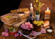 La vie toujours avec le vieux livre, les herbes curatives, les fleurs et les bougies Photo stock