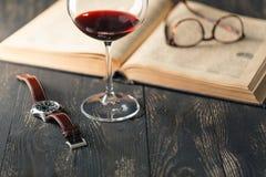 La vie toujours avec le vin rouge et les vieux livres sur la vieille table en bois dans le rétro style Image stock