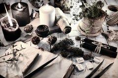 La vie toujours avec les bougies noires et blanches, les runes, les cônes et le livre ouvert de journal intime sur la table photo libre de droits