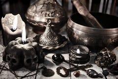 La vie toujours avec les bougies noires, le dishware antique en métal, la cuvette de chant et la clé photos stock