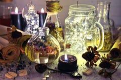 La vie toujours avec les bouteilles lumineuses, les rouleaux de papier, les runes, les graines et la bougie noire images libres de droits