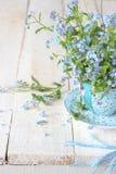 La vie toujours avec les fleurs minuscules de ressort dans une tasse bleue image libre de droits