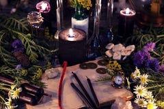 La vie toujours avec les herbes et les fleurs curatives, le vieux livre et les bougies noires image stock
