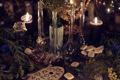 La vie toujours avec les objets rituels d'alchimie, les vieilles bouteilles, les herbes et les bougies noires photo stock