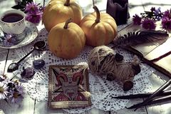 La vie toujours avec la poupée de vaudou, la carte de tarot de diable, la tasse de thé et les potirons photographie stock