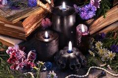La vie toujours avec trois bougies noires, vieux livres, cartes de tarot et herbes avec des fleurs images stock