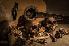 La vie toujours avec trois crâne et os au-dessus du fond de guitare Images libres de droits
