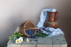 La vie toujours avec un vase à argile et une serviette, un panier avec les baies mûres sur la table images stock