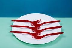 La vie toujours avec une fourchette en plastique et un plat sur colorés Photos stock
