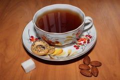 La vie toujours avec une tasse de thé, un morceau de sucre et des amandes Photos libres de droits