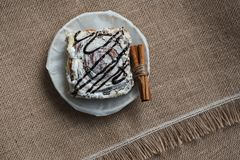 La vie toujours des épices et des bonbons culinaires Un gâteau doux d'un plat blanc de porcelaine avec des bâtons de cannelle sur Photo libre de droits