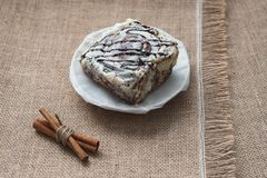 La vie toujours des épices et des bonbons culinaires Un gâteau doux d'un plat blanc de porcelaine avec des bâtons de cannelle sur Images libres de droits