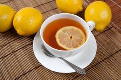 La vie toujours des citrons frais sur une serviette en bambou avec la tasse de thé Image libre de droits