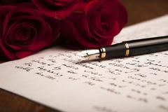 La vie toujours des roses d'un stylo-plume, de papier et de fleurs Photographie stock