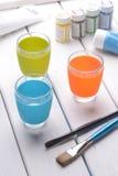 La vie toujours des tasses, des brosses et de la peinture colorées sur une table en bois blanche photos libres de droits