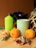 La vie toujours - deux citrons, deux coquilles de mer, bougie décorative verte et une tasse sur une table Image libre de droits