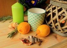 La vie toujours - deux citrons sur une table avec la bougie décorative verte et deux coquilles de mer Photos stock