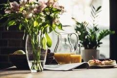 La vie toujours du journal, des fleurs et du petit déjeuner avec les gâteaux et le jus sur la table de cuisine dans l'avant photos stock
