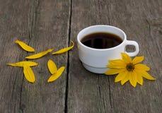 La vie toujours par tasse blanche de café, d'une fleur jaune et de pétales Photo libre de droits
