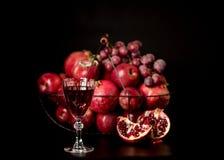 La vie toujours sur un fond foncé Vin et x28 ; liquor& x29 ; verres, fruits a photographie stock