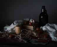 La vie toujours, vintage tomates-cerises, vieille bouteille avec l'huilerie et le couteau argenté sur une table en bois photographie stock